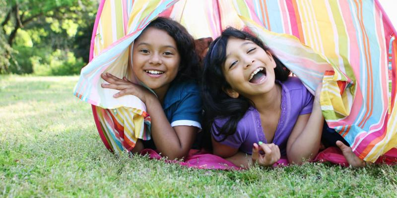 girls playing in tent outside