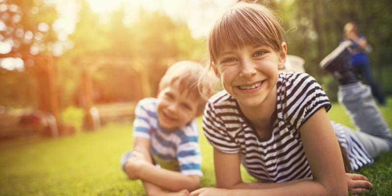 young boy and girl laying in the grass in backyard